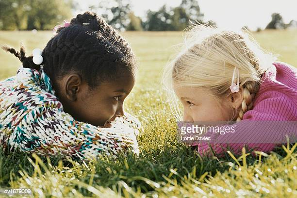 Two Girls Lying in a Field Face to Face