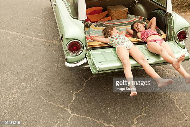 two girls lying in estate car - zus stockfoto's en -beelden