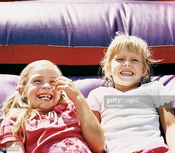 Two Girls Lying in Front of a Bouncy Castle
