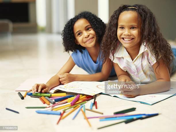 two girls (4-7) lying in front of colouring books, smiling - colouring bildbanksfoton och bilder