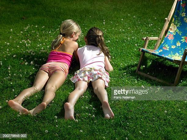 two girls (4-6) lying in grass, talking, rear view - girls with short skirts - fotografias e filmes do acervo