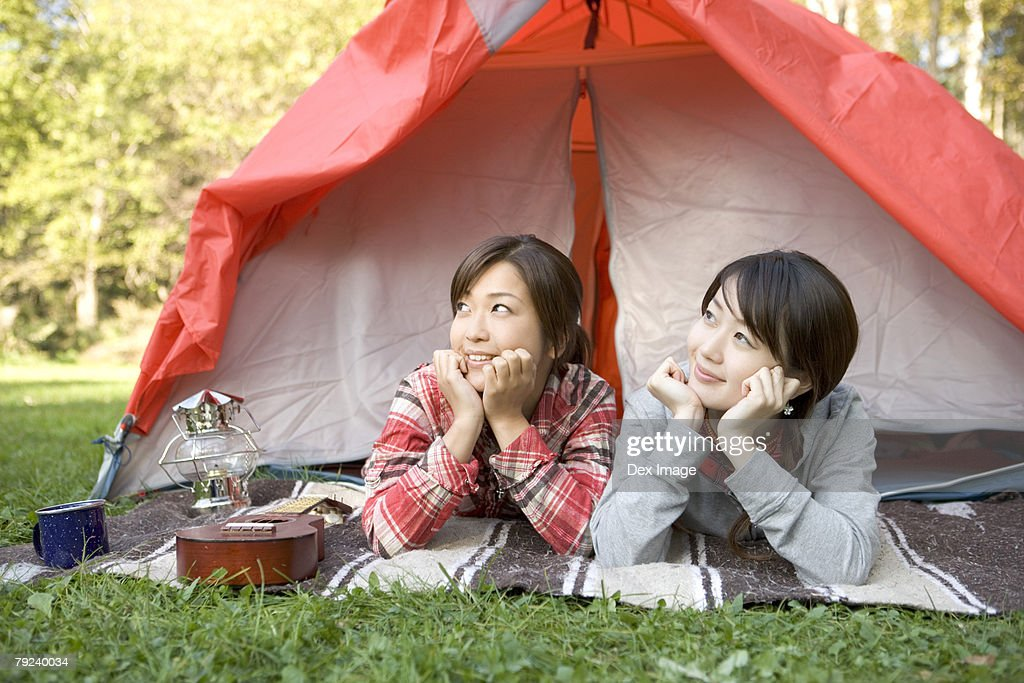 Two girls lying in tent : Stock Photo