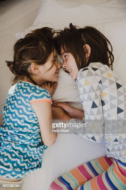 two girls lying on bed staring into each other's eyes - nur kinder stock-fotos und bilder