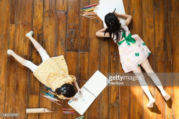 Two girls lying on floor drawing