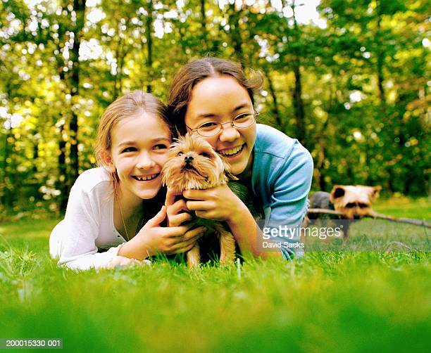 Two girls (8-13) lying on grass, holding dog, portrait