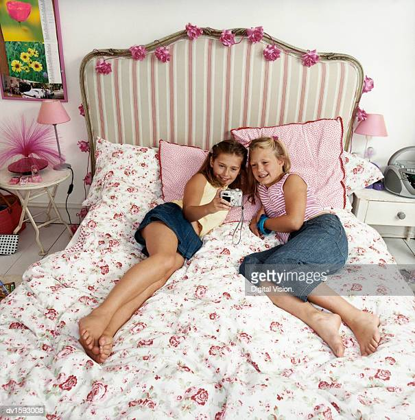 two girls lying side by side on a bed photographing themselves - little girls bare feet stock photos and pictures