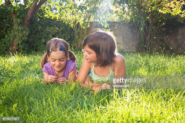 Two girls lying side by side on a meadow
