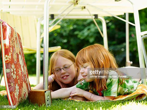 Two girls lying under outdoor table and listening to the radio