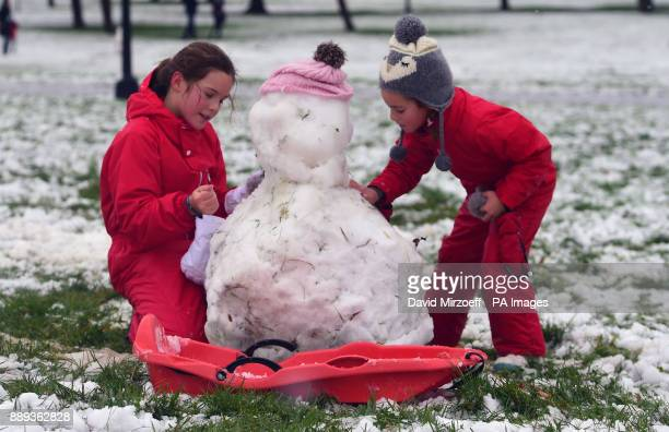 Two girls make a snowman on Primrose Hill in London as heavy snowfall across parts of the UK is causing widespread disruption closing roads and...