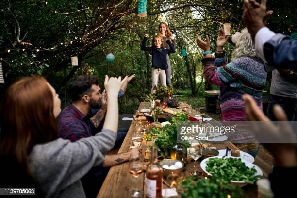 two girls making a speech on a garden party - gartenparty stock-fotos und bilder
