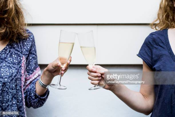 Two girls making a toast with two flutes of champagne