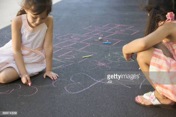 Two girls making chalk drawings