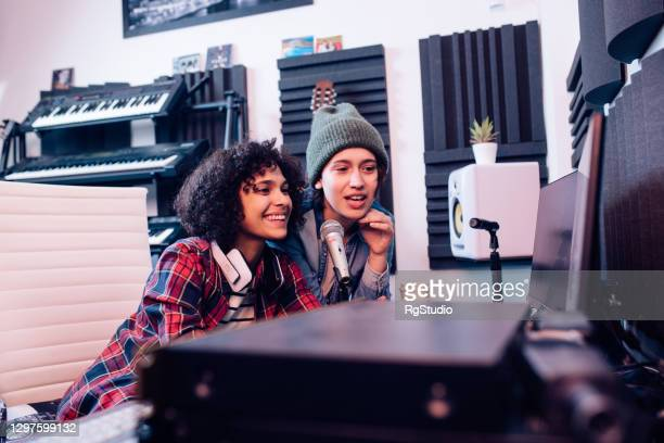 two girls mixing music on the computer at the music studio - singer songwriter stock pictures, royalty-free photos & images