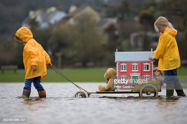 Two girls (7-9) moving doll house on cart through water, side view