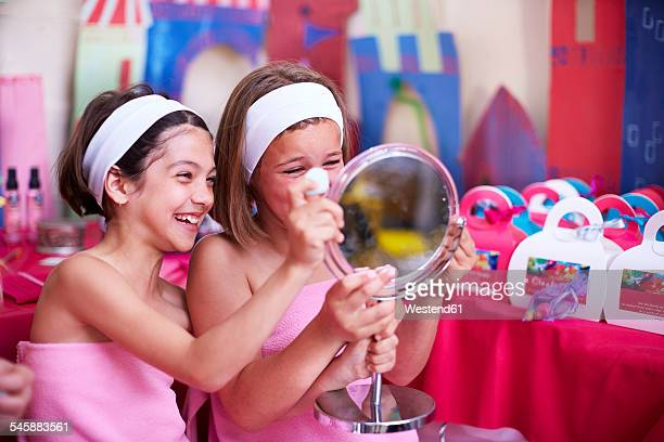 Two girls on a beauty farm looking in mirror