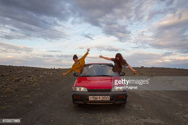 Two girls on a car on the road during a road trip through Iceland in the evening