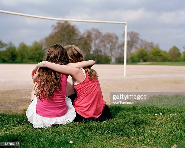 two girls on a playing field hugging - girls stock pictures, royalty-free photos & images