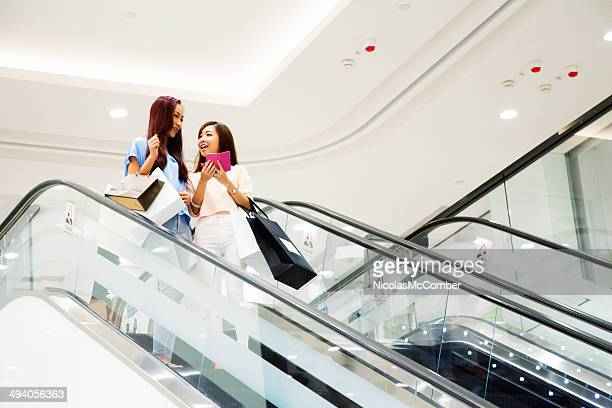 Two girls on an escalator in shopping mall