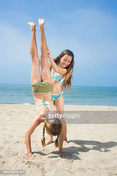 Two girls (9-11) on beach, one girl helping friend do handstand