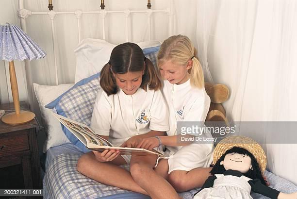 two girls (6-9) on bed reading comic, elevated view - alleen meisjes stockfoto's en -beelden