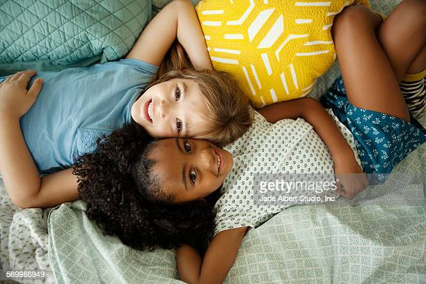 Two girls on bed smiling