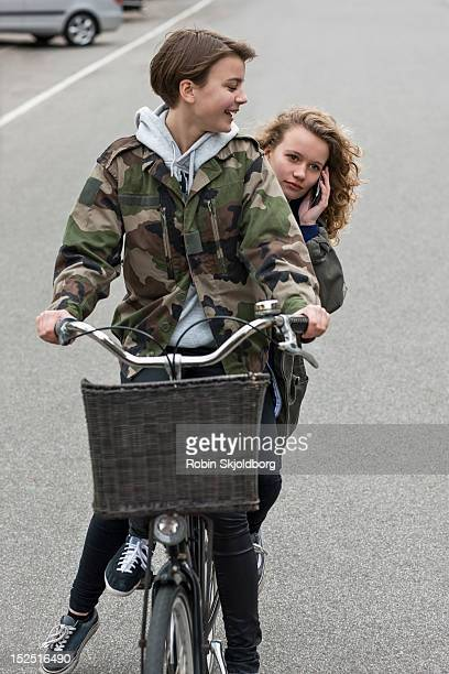 two girls on bicycle, one girl with mobile - robin skjoldborg stock pictures, royalty-free photos & images