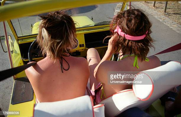 Two girls on holiday driving a yellow open-top Mini Moke jeep Portugal 2000's