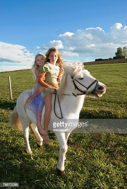 Two girls on horse back