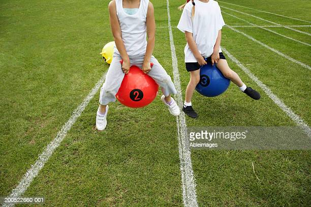 Two girls (6-8) on inflatable hoppers on grass running track