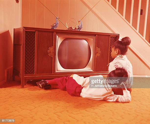 Two girls on living room floor, watching television. (Photo by H. Armstrong Roberts/Retrofile/Getty Images)