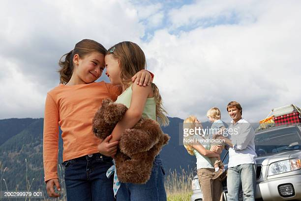 two girls (6-8 years) on road trip with family, smiling at each other - 30 39 years stockfoto's en -beelden