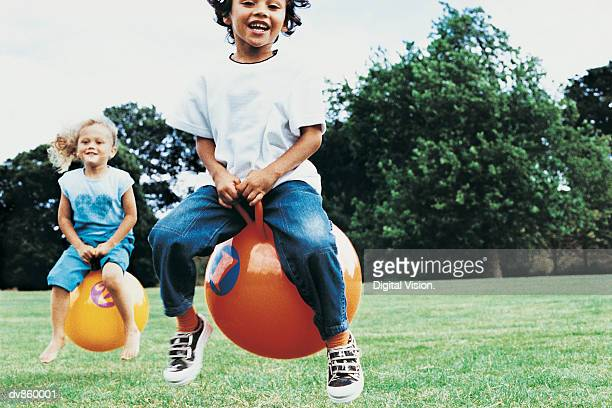 Two Girls on Space Hoppers in the Park