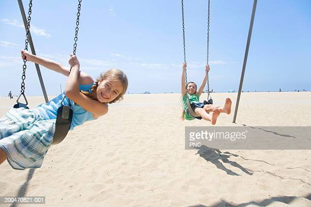 Two girls (9-11) on swings on beach