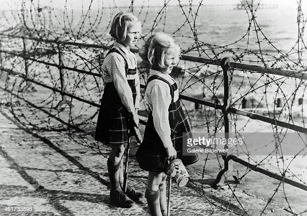 Two girls on the south coast of England look out toward the beach through a barbed wire fence constructed as part of Britain's coastal defenses 1940...