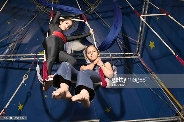 Two girls (11-15) on trapeze, portrait, low angle view