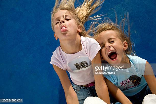 two girls (5-6), one shouting, one poking tongue out, close-up - girls open mouth stock photos and pictures