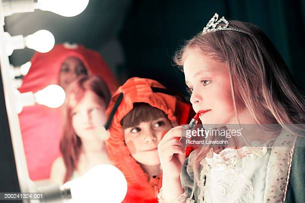 Two girls (5-8), one watching friend applying lipstick in stage mirror