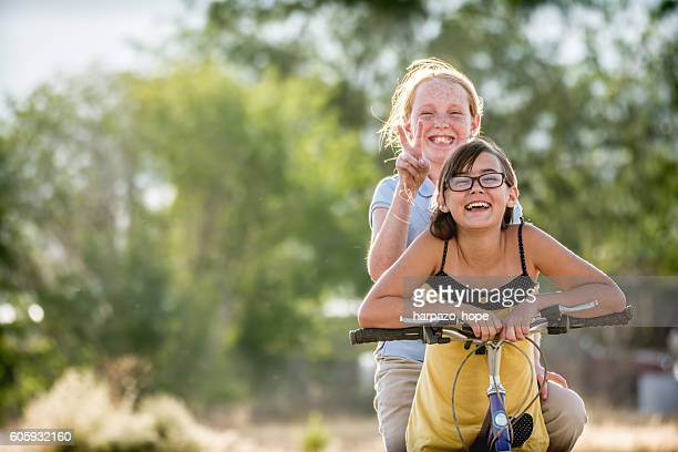 Two girls outside with a bicycle.