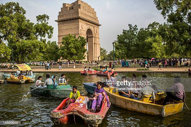 Two girls paddle the boat faster with their feet to avoid a collision in a pond at the India Gate monument on June 2 2012 in New Delhi India A Heat...