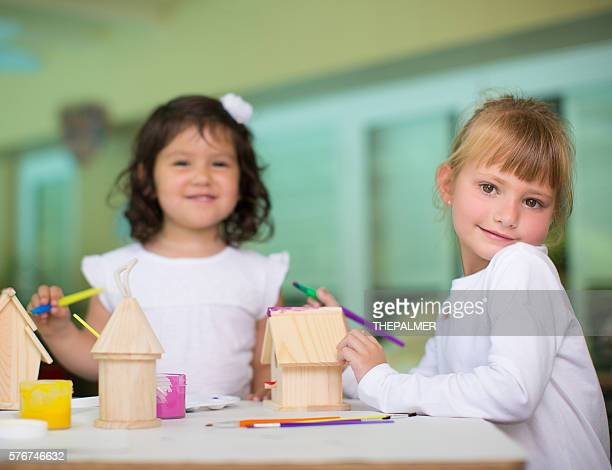 Two girls painting little wooden houses