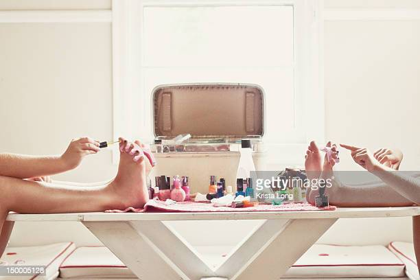Two girls painting their toenails.