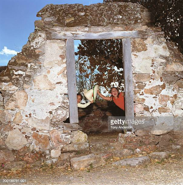 two girls (8-10) peeking out of doorway, smiling, portrait - little girl getting undressed stock pictures, royalty-free photos & images