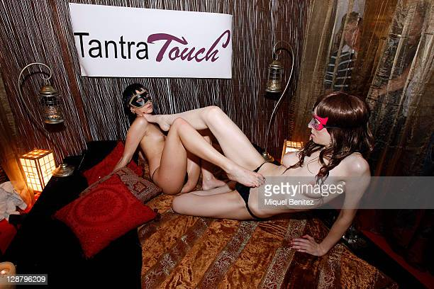 Two girls perform a Tantra massage in a stand at the Barcelona Erotic Fair on October 8 2011 in Barcelona Spain