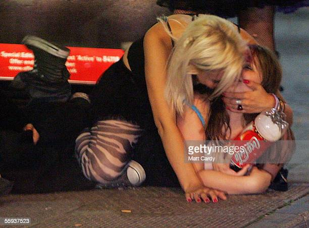 Two girls play around while lying on the floor in Bristol City Centre on October 15, 2005 in Bristol, England. Pubs and clubs are preparing for the...