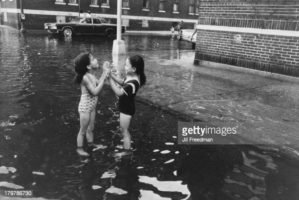 Two girls play in a flooded street in the South Bronx New York City 1975