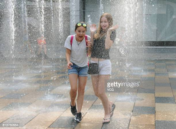Two girls play in the music fountain at Sanlitun on July 12 2017 in Beijing China The dog days of summer started from July 12 in China