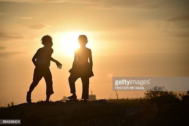 TOPSHOT Two girls play on a small wall during sunset in a neighborhood of the commune of Cite Soleil PortauPrince on August 22 2016 / AFP / HECTOR...