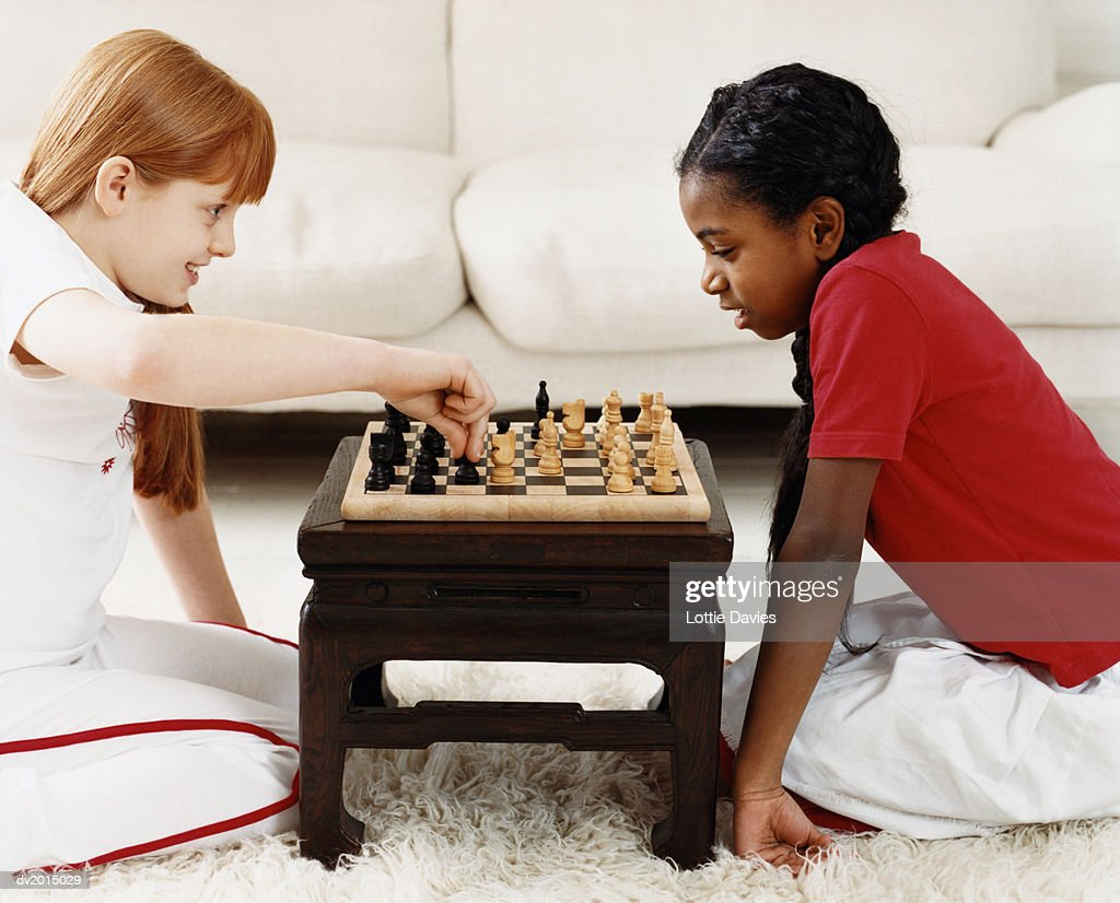 Two Girls Playing a Game of Chess in a Living Room : Stock Photo