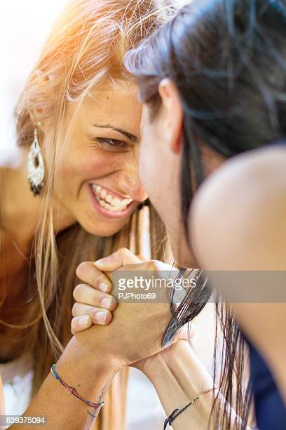 two girls playing arm wrestling - female wrestling holds stockfoto's en -beelden