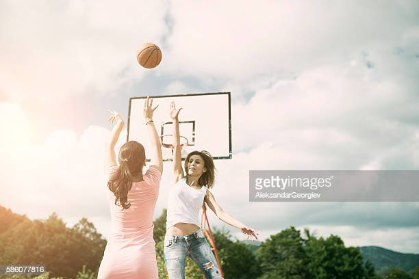 Two Girls Playing Basketball on Outdoor Court